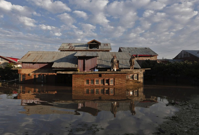 Kashmiri men stand on the roof of their flooded house as they wait to be rescued by Indian army soldiers in Srinagar September 10, 2014. Flood waters started receding in Indian Kashmir on Wednesday, giving rescue teams a chance to reach tens of thousands of villagers stranded by the heaviest rainfall in half a century. Floods and landslides triggered by days of rain in the disputed Himalayan region have killed at least 450 people in India and Pakistan and cut off more than one million people from basic services. (Adnan Abidi/Reuters)