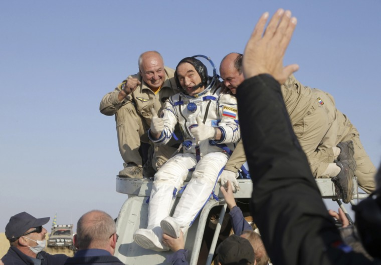 Russian space agency rescue team members help Russian cosmonaut Alexander Skvortsov out of the Russian Soyuz TMA-12M space capsule shortly after he landed southeast of Dzhezkazgan September 11, 2014. Two Russian cosmonauts and a NASA astronaut returned to Earth on Wednesday, capping a nearly six-month stay aboard the International Space Station. Riding inside a Russian Soyuz capsule, former station commander Steve Swanson and cosmonauts Skvortsov and Oleg Artemyev landed southeast of Dzhezkazgan, Kazakhstan at 8:23 a.m. Thursday (10:23 p.m. EDT Wednesday/0223 GMT). REUTERS/Maxim Shipenkov/Pool