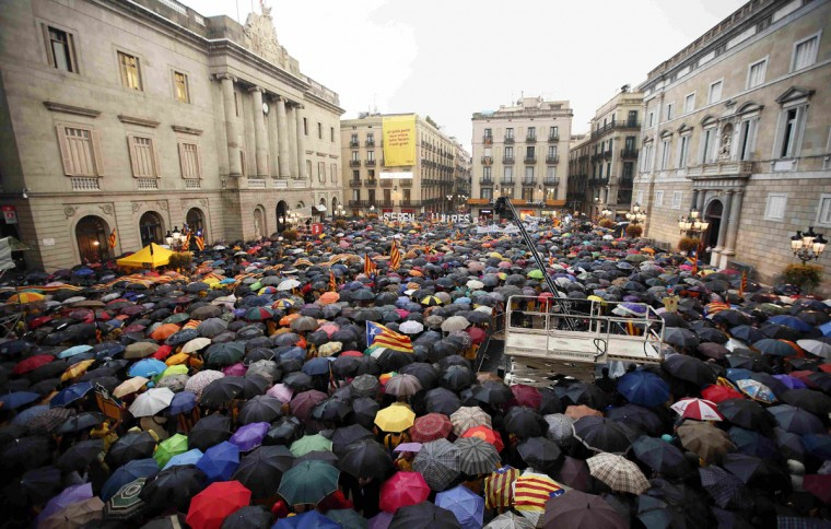"""Catalan pro-independence supporters protest against the Spanish Constitutional Court, in front of the Generalitat de Catalunya in Barcelona September 30, 2014. Catalonia's regional government said on Tuesday it would temporarily suspend formal campaigning for a referendum on independence from Spain, after Madrid filed a legal appeal to stop the vote taking place. Madrid argues that the vote, called by Catalan leader Artur Mas for November 9, would breach Spain's rule of law because it would be held in Catalonia alone, rather than in the whole of Spain. It filed an appeal on Monday with the Constitutional Court to stop it going ahead, which Catalan officials now want to try and overturn. The words read: """"We will be free"""". (REUTERS/Albert Gea)"""