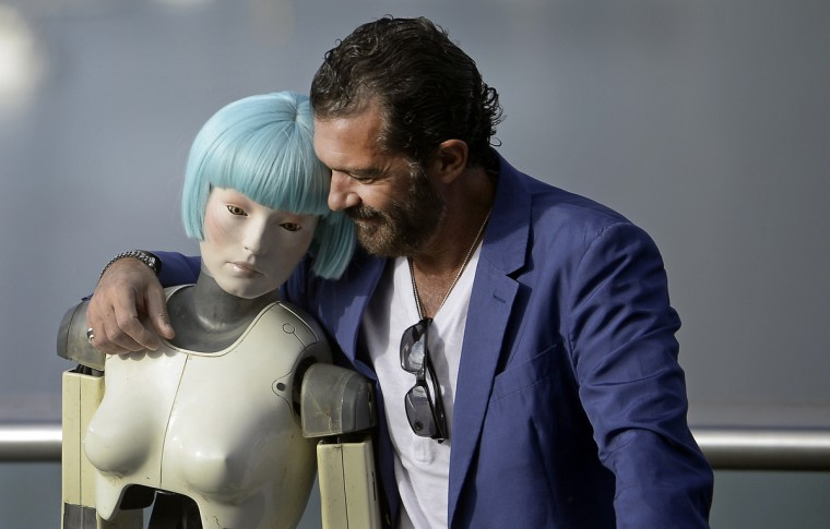 Spanish actor Antonio Banderas embraces a robot used in the film Automata during a photocall on the third day of the 62nd San Sebastian Film Festival. Banderas stars in and produced the science fiction film, which is part of the festival's official section. (Vincent West/Reuters)