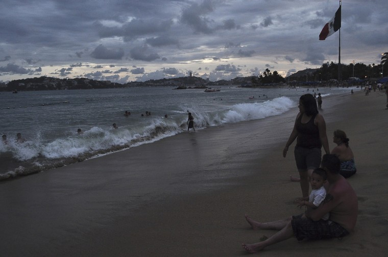 People spend time at the beach in Acapulco, as Hurricane Odile churns far off shore September 14, 2014. The Mexican government declared a hurricane warning for southern Baja and a tropical storm warning for parts of the Pacific coast. (Claudio Vargas/Reuters)