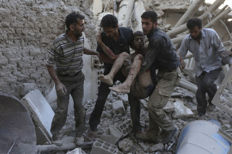 Men carry an injured man, after what activists claim was five air strikes by forces loyal to Syria's President Bashar al-Assad in Douma, eastern al-Ghouta, near Damascus September 11, 2014. REUTERS/Bassam Khabieh