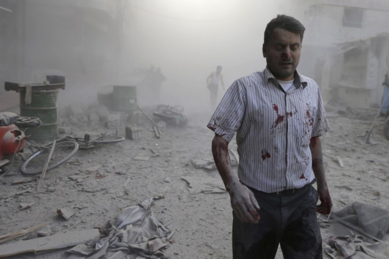 A man reacts amid damage after what activists said were five air strikes by forces loyal to Syria's President Bashar al-Assad in Douma, eastern al-Ghouta, near Damascus September 11, 2014. REUTERS/Bassam Khabieh