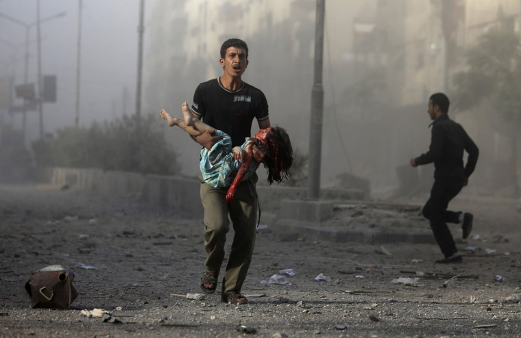 A man carries an injured girl, after what activists claim was five air strikes by forces loyal to Syria's President Bashar al-Assad in Douma, eastern al-Ghouta, near Damascus September 11, 2014. REUTERS/Bassam Khabieh