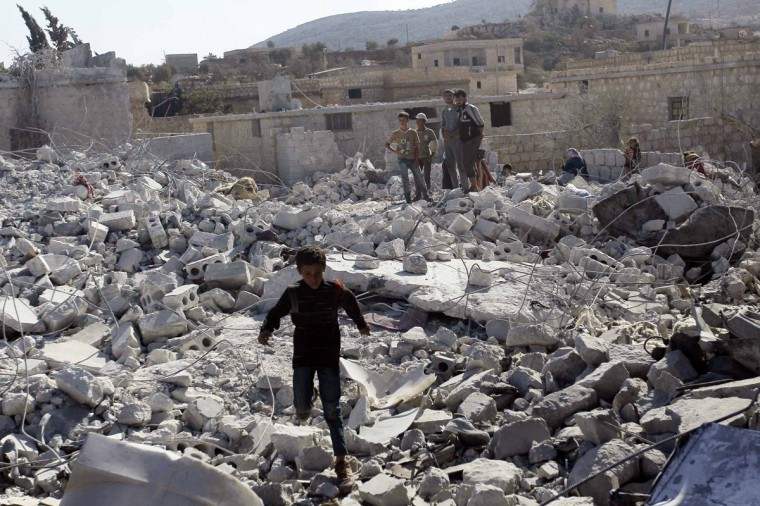 Residents inspect damaged buildings in what activists say was a U.S. strike, in Kfredrian, Idlib province September 23, 2014. (Abdalghne Karoof/Reuters)