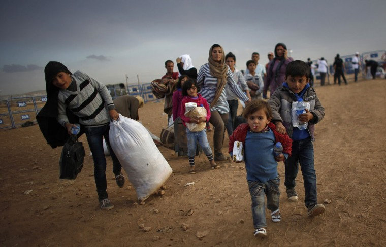 Kurdish Syrian refugees carry their belongings after crossing the Turkish-Syrian border near the southeastern town of Suruc in Sanliurfa province September 25, 2014. Kurdish forces in northern Syria pushed back an advance by Islamic State fighters towards a strategic town on the Turkish border on Thursday and appealed for U.S.-led air strikes to target the insurgents' tanks and heavy armaments. Islamic State launched a new offensive to try to capture the border town of Kobani more than a week ago, besieging it from three sides. At least 140,000 Kurds have fled the town and surrounding villages since Friday, crossing into Turkey. (REUTERS/Murad Sezer)