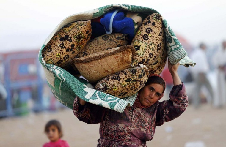 A Syrian Kurdish woman carries her belongings after crossing into Turkey near the southeastern town of Suruc in Sanliurfa province September 22, 2014. Syrian Kurds battled to defend a key border town from an Islamic State advance on Monday as Kurdish youths from neighbouring Turkey rushed to their aid, heightening the pressure on Ankara to act against the Islamist insurgents. In Turkey, which is struggling to manage an influx of more than 130,000 Syrian Kurdish refugees since Friday, security forces fired tear gas and water cannon at hundreds of Kurdish protesters who accuse Ankara of favouring Islamic State against the Kurds. (Murad Sezer/Reuters)