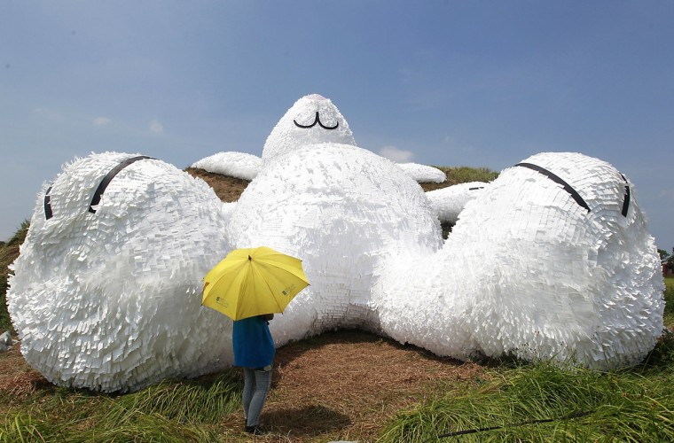 "A person stands in front of a 25.3-meter-long giant rabbit designed by Dutch artist Florentijn Hofman at an old aircraft hangar as part of the Taoyuan Land Art Festival in Taoyuan, northern Taiwan. The rabbit is named ""Moon rabbit"" for the coming Mid-Autumn Festival or the Moon Festival and will be displayed from September 4 to 14 at the Taoyuan military base. (Pichi Chuang/Reuters)"