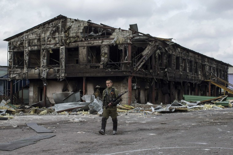 A pro-Russian rebel walks in front of a factory destroyed during recent shelling, in the town of Nizhnaya Krinka, eastern Ukraine, September 23, 2014. (Marko Djurica/Reuters)