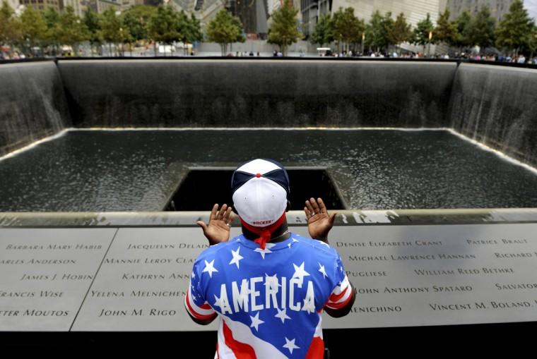 Albert Biatta, of Queens, New York, prays while standing in front of the inscribed name of his uncle Antoine Biatta at the edge of the North Pool during memorial observances held at the site of the World Trade Center in New York, September 11, 2014.
