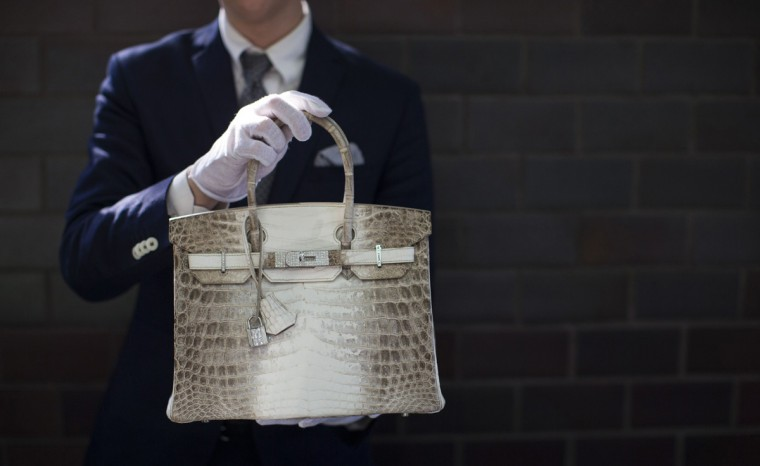An employee holds an Hermes diamond and Himalayan Nilo Crocodile Birkin handbag at Heritage Auctions offices in Beverly Hills, California September 22, 2014. The handbag has 242 diamonds with a total of 9.84 carats. (Mario Anzuoni/Reuters)