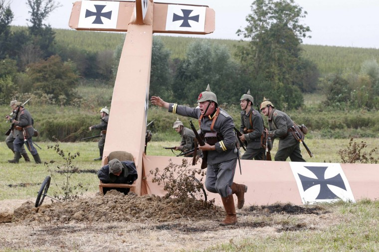 British history enthusiast portraying German 'Feldwebelleutnant' officer Fritz Brandt (front) leads members of the Sturmabteilungbrandt group during the re-enactment of the First Battle of the Marne, which took place a century ago, at Chauconin-Neufmontiers, Eastern Paris September 6, 2014. Dozens of volunteers dressed in French and German military uniforms recreated the battle from two trenches dug out by local residents to mark the 100th anniversary of the start of the First World War (WWI). Picture taken September 6, 2014. (Charles Platiau /Reuetrs)