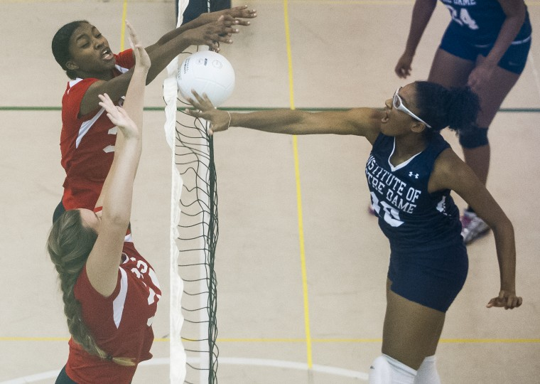Institute of Notre Dame's Ja'Lyn Armstrong tries to hit past the block of Roland Park County School's Bailey Andrews (top) and Mia Thomas during the prep volleyball matchup between Roland Park Country School and the Institute of Notre Dame in Baltimore Wednesday, Sept. 17. (Photo by Scott Serio, Baltimore Sun Media Group)