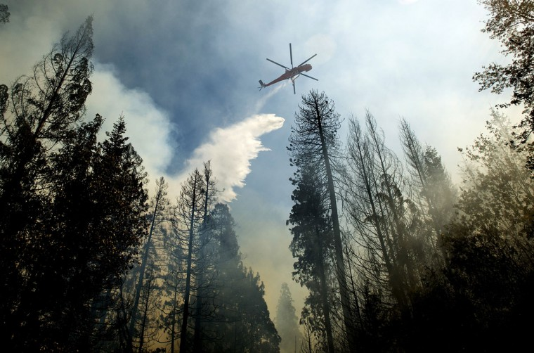 A helicopter drops water while battling the King Fire near Fresh Pond, California on September 16, 2014. (REUTERS/Noah Berger)
