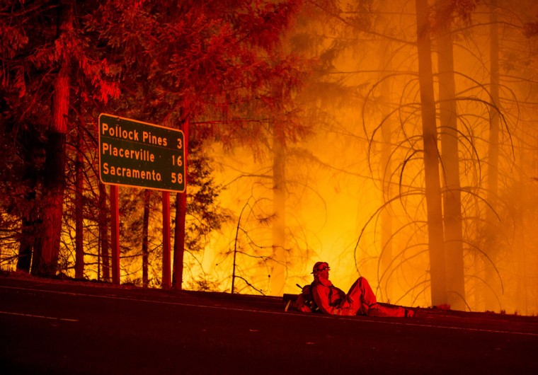 A firefighter battling the King Fire watches a backfire burn along Highway 50 in Fresh Pond, California on September 16, 2014. (REUTERS/Noah Berger)