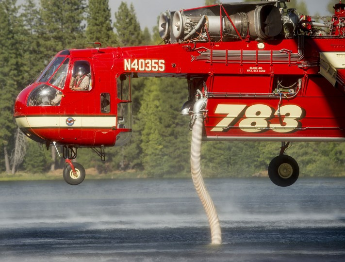 A helicopter draws water from a lake while battling the King Fire in Pollock Pines, California on September 17, 2014. (REUTERS/Noah Berger)