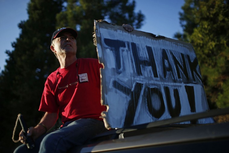Herve Leconte of Camino holds a thank you sign along Highway 50, for firefighters battling the King Fire northeast of Sacramento, California on September 18, 2014. (REUTERS/Stephen Lam)