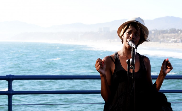 A singer performs on the Santa Monica Pier with the beach and ocean in the background.
