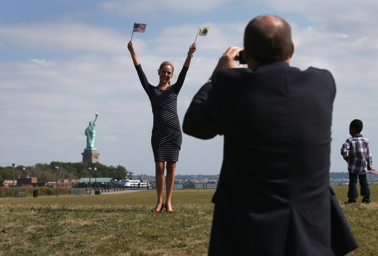 Nicole Annete Flood from Mexico poses for photos in front of the Statue of Liberty following a naturalization ceremony at Liberty State Park in Jersey City, New Jersey. Forty immigrants from 18 different countries became American citizens at the event, held by U.S. Citizenship and Immigration Services (USCIS), on Constitution and Citizenship Day. This week USCIS will have naturalized more than 27,000 new citizens at 160 ceremonies nationwide. (John Moore/Getty Images)