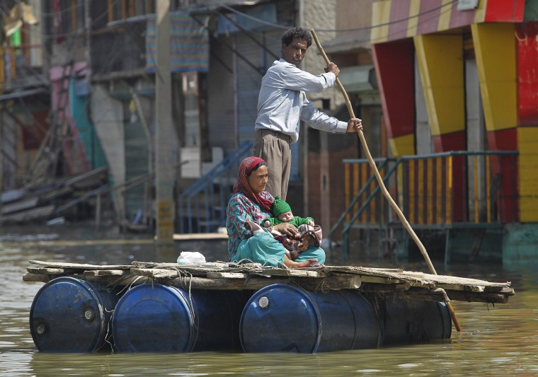 A Kashmiri man rows a makeshift raft carrying a woman and a child through the flood waters in Srinagar. Both the Indian and Pakistani sides of the disputed Himalayan region have seen extensive flooding this month with Srinagar particularly hard hit. Hundreds of people have been killed and tens of thousands are homeless. (Danish Ismail/Reuters)