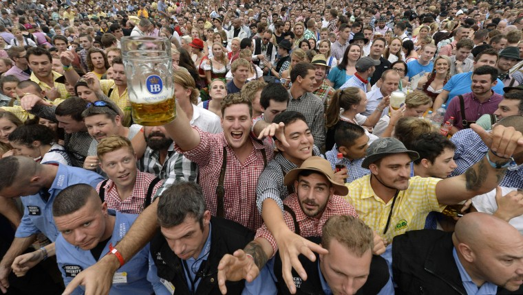 Visitors celebrate with first beer mugs at the opening of the traditional Bavarian Oktoberfest festival at the Theresienwiese in Munich, southern Germany. Germany's world-famous Oktoberfest kicks off with millions of revellers set to soak up the frothy atmosphere in a 16-day extravaganza of lederhosen, oompah music and, of course, beer. (Christof Stache/AFP-Getty Images)