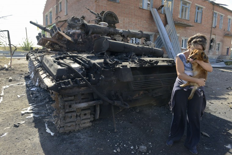 A woman holds a dog beside a destroyed tank in the courtyard of the local kindergarten in the village of Talakovka, some 22 kilometres northeast of Mariupol, a day after Kiev and pro-Russian rebels signed a ceasefire after five months conflict which has plunged relations between Russia and the West into their worst crisis since the Cold War. Pro-Russian rebels and the Ukrainian military accused each other on September 6 of breaking a tenuous Kremlin-backed truce only hours after it came into force at 1500 GMT on September 5 across the war-battered east. But Ukrainian President Petro Poroshenko said on September 6 that he and Russian leader Vladimir Putin had agreed that the ceasefire between Kiev and separatist rebels was largely holding. Alexander Khudoteply/AFP-Getty Images)