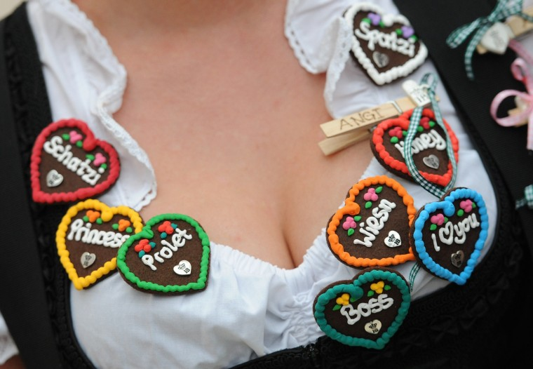 A seller wears bagdes in the shape of gingerbread hearts on the neckline of her dirndl dress during the opening of the traditional Bavarian Oktoberfest festival at the Theresienwiese in Munich, southern Germany. Germany's world-famous Oktoberfest kicks off with millions of revellers set to soak up the frothy atmosphere in a 16-day extravaganza of lederhosen, oompah music and, of course, beer. (Andreas Gebert/AFP-Getty Images)
