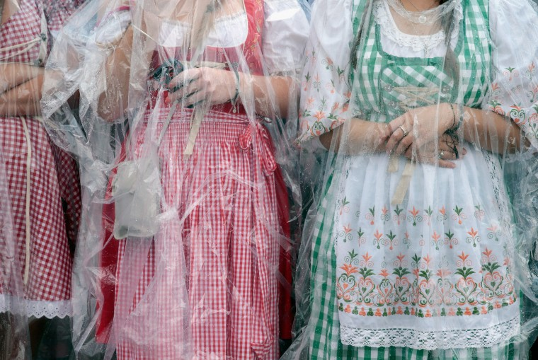 Revellers dressed in traditional Bavarian 'Dirndl' shelter themselves from the rain waiting for the opening parade during the day 01 of the 2014 Oktoberfest in Munich, Germany. The 181st Oktoberfest will be open to the public from September 20 through October 5 and traditionally draws millions of visitors from across the globe to the the world's largest beer festival. (Johannes Simon/Getty Images)