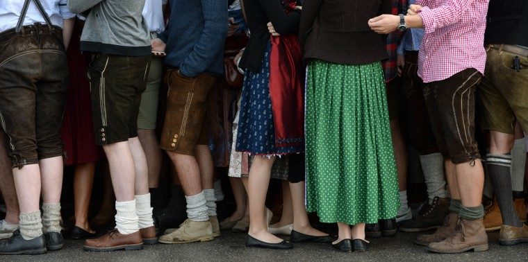 Visitors wearing traditionlal Bavarian costumes wait outside of festival tents ahead the opening of the traditional Bavarian Oktoberfest festival at the Theresienwiese in Munich, southern Germany. Germany's world-famous Oktoberfest kicks off with millions of revellers set to soak up the frothy atmosphere in a 16-day extravaganza of lederhosen, oompah music and, of course, beer. (Christof Stache/AFP-Getty Images)