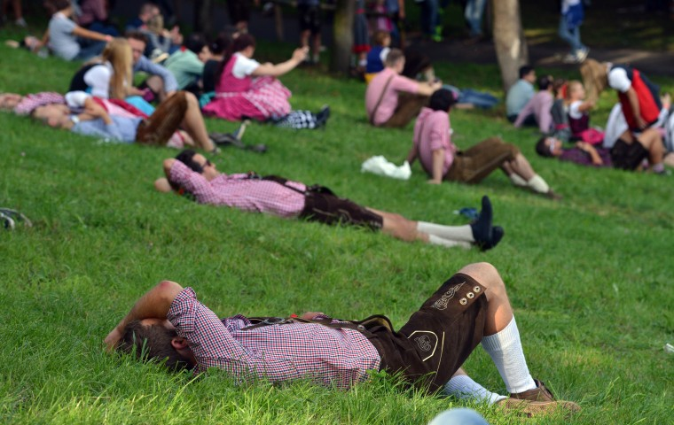 Drunken or tired visitors in traditional bavarian clothes take a rest during the opening day of the 2014 Oktoberfest in Munich, Germany. Oktoberfest is the world's biggest beer bash and draws millions of visitors. The annual event lasts for three weeks and will open its doors on September 20. (Joerg Koch/Getty Images)
