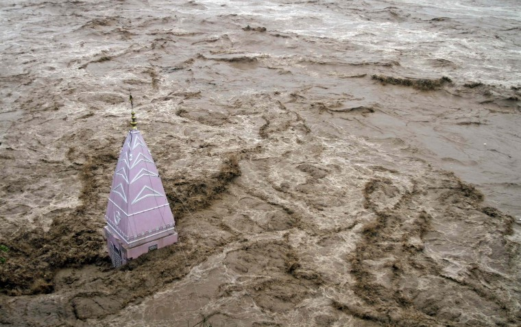A temple stands amid the waters of the overflowing river Tawi during heavy rains in Jammu. Authorities declared a disaster alert in the northern region after heavy rain hit villages across the Kashmir valley, causing the worst flooding in two decades. (Mukesh Gupta/Reuters)