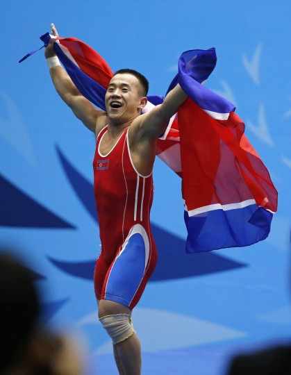 North Korea's Om Yun Chol reacts on stage after winning the men's 56kg weightlifting competition at the Moonlight Festival Garden during the 17th Asian Games in Incheon. Om broke his own clean and jerk world record on the way to winning his country's first gold medal of the Asian Games in Incheon on Saturday. The North Korean weightlifter who won a gold medal at the London Olympics, raised 170 kilograms to better his old record by 1kg in the men's 56kg class. He earlier lifted 128kg in the snatch for a combined total of 298kg. (Jason Reed/reuters)