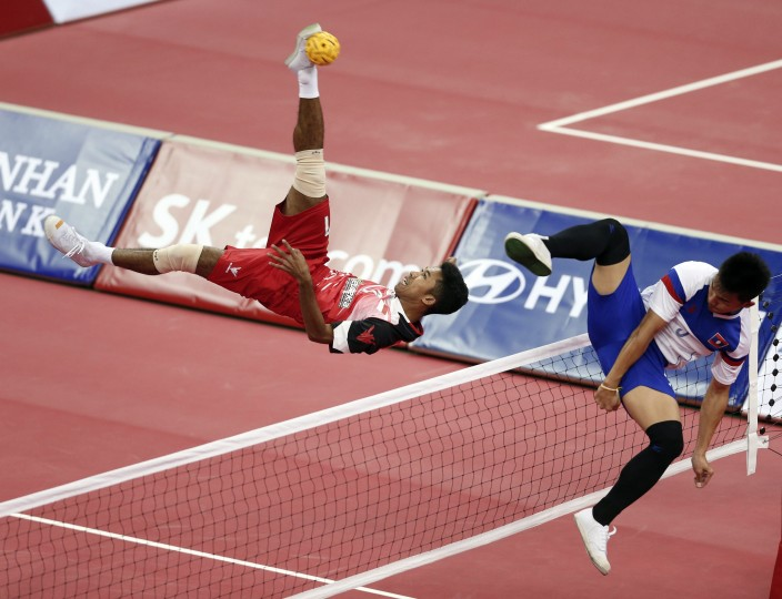 Indonesia's Syamsul Hadi strikes the ball as Laos' Noum Souvannalith defends during their men's doubles sepak takraw match at Bucheon Gymnasium during the 17th Asian Games in Incheon. (Olivia Harris/Reuters)