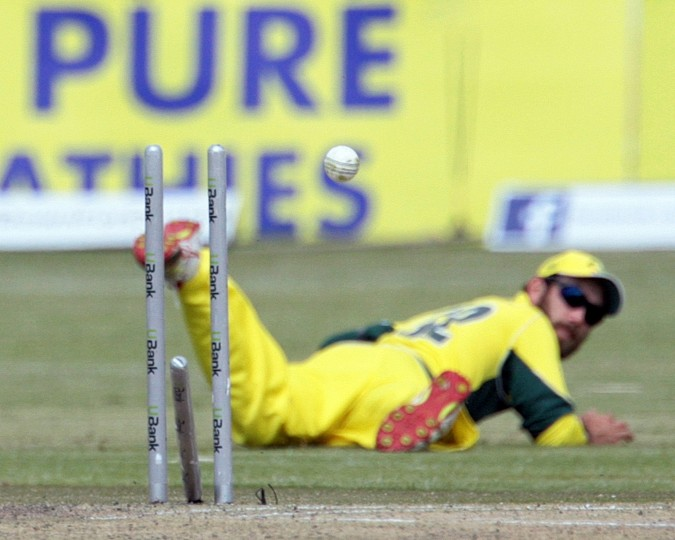 Australia's fielder Glenn Maxwell strikes the stumps in a failed run out attempt on batsman Hashim Amla during the final match of the one day international tri-series between Australia and South Africa, the series played at the Harare Sports Club included hosts Zimbabwe. (Jekesai Njikizana/AFP-Getty Images)
