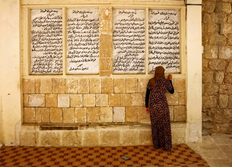 A displaced woman from the minority Yazidi sect, who fled violence in the Iraqi town of Sinjar, worships at their main holy temple in Lalish in Shikhan. Followers of an ancient religion derived from Zoroastrianism, the Yazidi fled their homeland in the Sinjar mountains as Islamic State militants, who see them as devil worshippers, seized towns and carried out mass killings in August. (Ahmed Jadallah/Reuters)