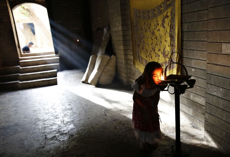 A displaced girl from the minority Yazidi sect, who fled violence in the Iraqi town of Sinjar, worships at their main holy temple Lalish in Shikhan. Followers of an ancient religion derived from Zoroastrianism, the Yazidi fled their homeland in the Sinjar mountains as Islamic State militants, who see them as devil worshippers, seized towns and carried out mass killings in August. (Ahmed Jadallah/Reuters)
