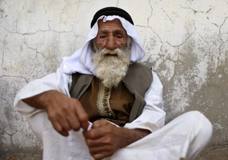 A displaced man from the minority Yazidi sect, who fled violence in the Iraqi town of Sinjar, sits out side the holy temple Lalish in Shikhan. Followers of an ancient religion derived from Zoroastrianism, the Yazidi fled their homeland in the Sinjar mountains as Islamic State militants, who see them as devil worshippers, seized towns and carried out mass killings in August. (Ahmed Jadallah/Reuters)