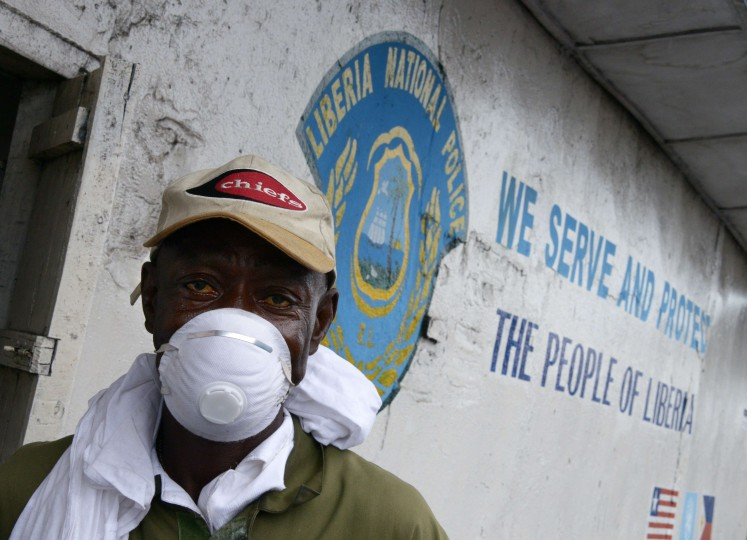 A Liberian policeman stands guard in Monrovia's West Point slum. The death toll from the Ebola epidemic has climbed above 2,000, the World Health Organisztion (WHO) said on September 5, as it voiced hopes a vaccine could be available in November. The deadly virus has claimed 2,097 lives out of 3,944 people infected in Liberia, Guinea and Sierra Leone, since emerging in December 2013, the UN's health organ said after a two-day crisis meeting in Geneva. (Dominique FagetAFP-Getty Images)