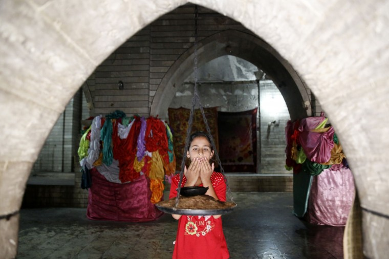 A displaced girl from the minority Yazidi sect, who fled violence in the Iraqi town of Sinjar, worships at their main holy temple in Lalish in Shikhan. Followers of an ancient religion derived from Zoroastrianism, the Yazidi fled their homeland in the Sinjar mountains as Islamic State militants, who see them as devil worshippers, seized towns and carried out mass killings in August. (Ahmed Jadallah/Reuters)