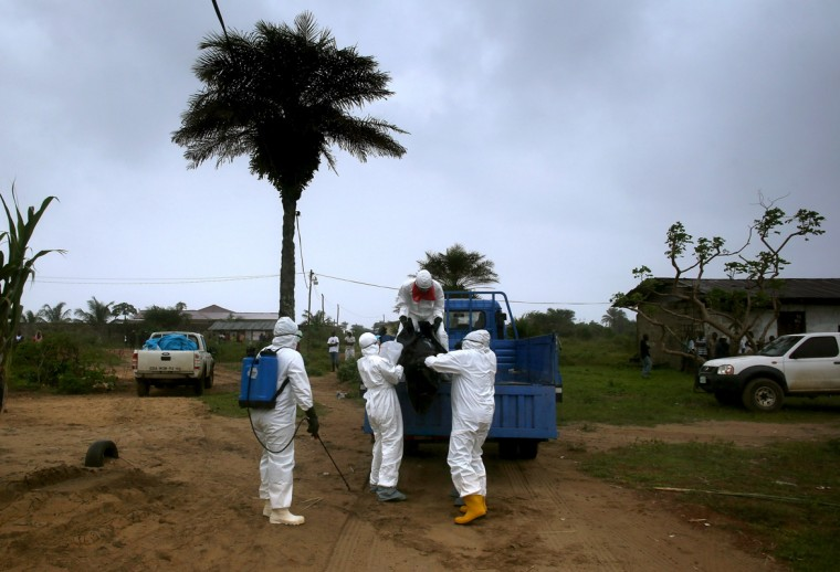 A Liberian burial team wearing protective clothing loads the body of a 60-year-old Ebola victim after retrieving him from his home on August 17, 2014 near Monrovia, Liberia. The epidemic has killed more than 1,000 people in four African countries, and Liberia now has had more deaths than any other country. (Photo by John Moore/Getty Images)