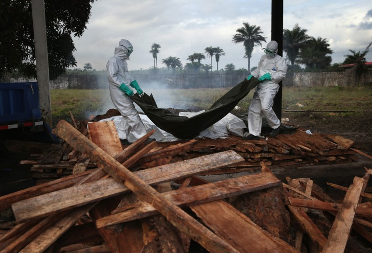 A burial team from the Liberian Ministry of Health unloads the bodies of Ebola victims onto a funeral pyre at a crematorium on August 22, 2014 in Marshall, Liberia. The Ebola epidemic has killed at least 1,350 people in West Africa and more in Liberia than any other country. (Photo by John Moore/Getty Images)