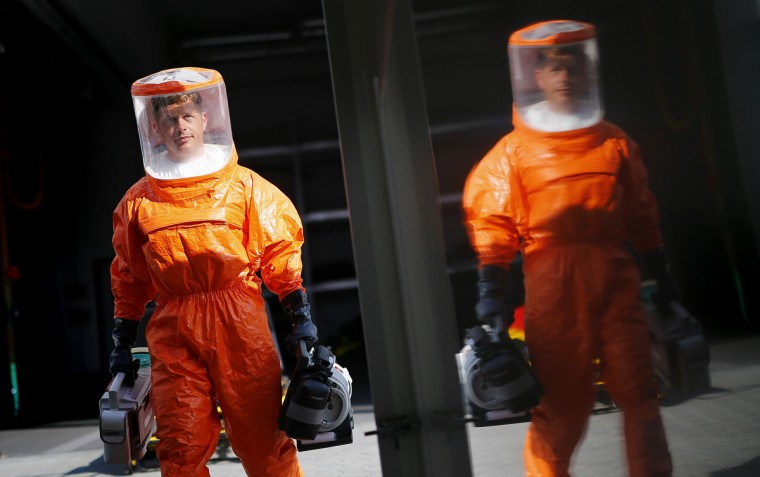 A fire brigade paramedic wearing a sealed protective suit is reflected in a special fire brigade ambulance, as he carries medical equipment into the vehicle during a drill for the crew, in Frankfurt August 21, 2014. The special ambulance is equipped to treat patients suffering from ebola and other highly infectious diseases. Ebola is one of the deadliest diseases known to humanity. It has no proven cure and there is no vaccine to prevent infection. The rigorous use of quarantine is needed to prevent its spread, as well as high standards of hygiene for anyone who might come into contact with the disease. (Kai Pfaffenbach/Reuters)