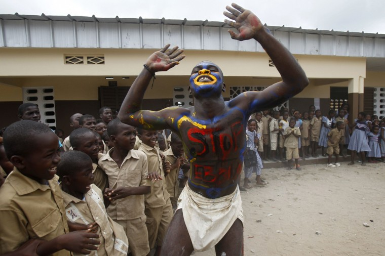 An actor, playing the role of a vaccine against the Ebola, performs in front of students during an awareness campaign against the virus at Anono school in Abidjan September 25, 2014. (Luc Gnago/Reuters)