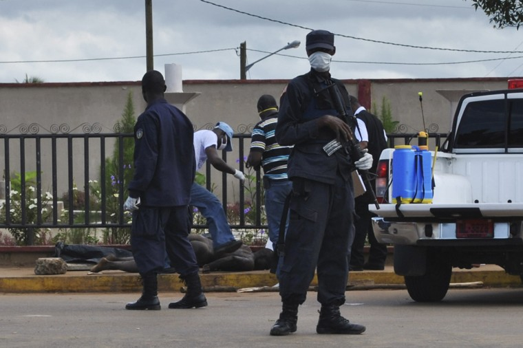 Police stand guard as officers test the body of a man for the Ebola virus, which according to police is standard protocol when bodies are discovered, in Monrovia September 27, 2014. (James Giahyue/Reuters)