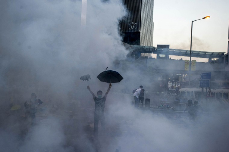 A pro-democracy demonstrator gestures after police fired tear gas towards protesters near the Hong Kong government headquarters on September 28, 2014. Police fired tear gas as tens of thousands of pro-democracy demonstrators brought parts of central Hong Kong to a standstill on September 28, in a dramatic escalation of protests that have gripped the semi-autonomous Chinese city for days. (Xaume Olleros/AFP/Getty Images)