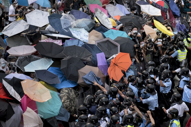Police clash with pro-democracy protesters near the government headquarters in Hong Kong on September 28, 2014. Police fired tear gas as tens of thousands of pro-democracy demonstrators brought parts of central Hong Kong to a standstill Sunday, in a dramatic escalation of protests that have gripped the semi-autonomous Chinese city for days. (Alex Ogle/AFP/Getty Images)
