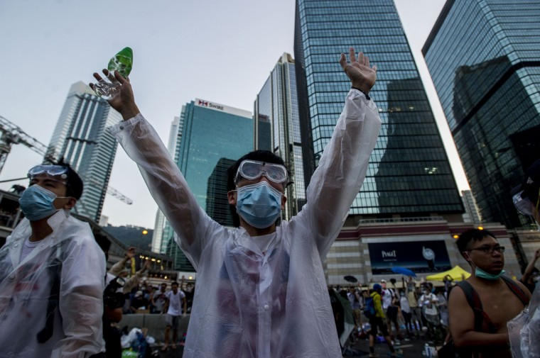 A pro-democracy demonstrator wearing a mask and goggles to protect against pepper spray and tear gas gestures during a rally near the Hong Kong government headquarters on September 28, 2014. Police fired tear gas as tens of thousands of pro-democracy demonstrators brought parts of central Hong Kong to a standstill on September 28, in a dramatic escalation of protests that have gripped the semi-autonomous Chinese city for days. (Xuame Olleros/AFP/Getty Images)