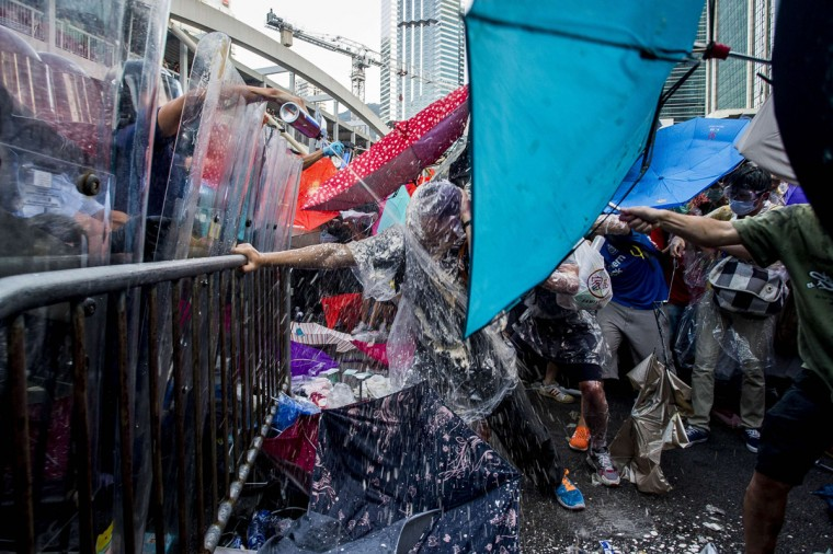 Pro-democracy demonstrators are sprayed with pepper spray during clashes with police officers during a rally near the Hong Kong government headquarters on September 28, 2014. Police fired tear gas as tens of thousands of pro-democracy demonstrators brought parts of central Hong Kong to a standstill on September 28, in a dramatic escalation of protests that have gripped the semi-autonomous Chinese city for days. (Xuame Olleros/AFP/Getty Images)