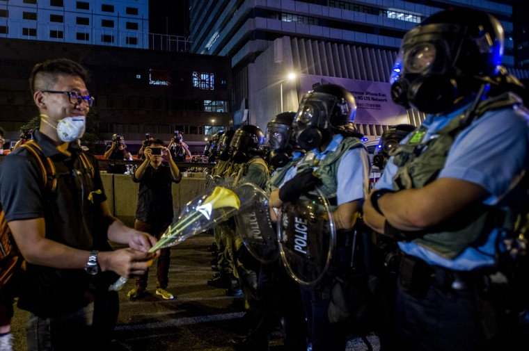 A demonstrator offers a flower to riot policemen during a pro-democracy protest in Hong Kong on September 28, 2014. Police fired tear gas as tens of thousands of pro-democracy demonstrators brought parts of central Hong Kong to a standstill in a dramatic escalation of protests that have gripped the semi-autonomous Chinese city for days. (Xuame Olleros/AFP/Getty Images)
