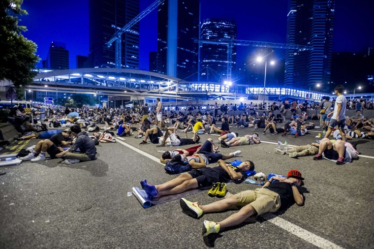Protesters rest following pro-democracy protests in Hong Kong on September 29, 2014. Police fired tear gas as tens of thousands of pro-democracy demonstrators brought parts of central Hong Kong to a standstill in a dramatic escalation of protests that have gripped the semi-autonomous Chinese city for days. (Xuame Olleros/AFP/Getty Images)